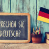 a chalkboard with the question sprechen sie deutsch? do you speak German with German flag